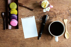 Colorful macaroons with coffee and blank note on wooden Royalty Free Stock Images