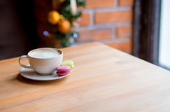 Colorful macaroons and coffee cup on window background stock images