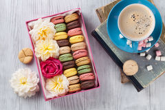 Colorful macaroons, coffee. Sweet macarons. Colorful macaroons and coffee on wooden table. Sweet macarons in gift box and flowers. Top view stock photography