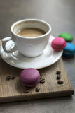 Colorful macaroons and coffee on wooden background Royalty Free Stock Images