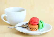 Colorful macaroons and cup of coffee with spoon Stock Photography
