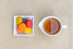 Colorful macaroons and a cup of tea Stock Photo