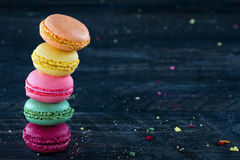 Colorful macaroons on a dark black wooden background Stock Photos