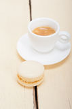 Colorful macaroons with espresso coffee. Over white wood table Stock Photos