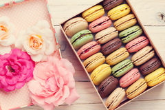 Colorful macaroons in a gift box and roses Royalty Free Stock Photo