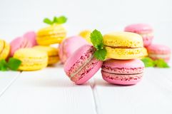 Colorful macaroons and mint leaves on white wooden background stock photos