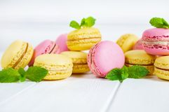Colorful macaroons and mint leaves on white wooden background royalty free stock images