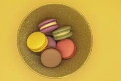 Colorful macaroons cakes on orange background royalty free stock image