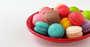 Colorful macaroons on red plate royalty free stock image