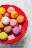 Colorful macaroons in red plate on gray wooden background Stock Photo