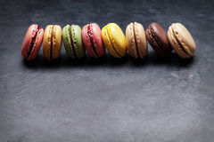 Colorful macaroons on stone table. Sweet macarons Stock Image