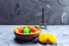 Colorful macaroons on stone table. Sweet macaroons in wooden dish. Copy space. Colorful macaroons on stone table. Sweet macaroons in wooden dish royalty free stock photo