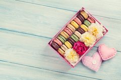 Colorful macaroons. Sweet macarons. Colorful macaroons on wooden table. Sweet macarons in gift box and hearts. Top view with copy space for your text. Toned royalty free stock photo