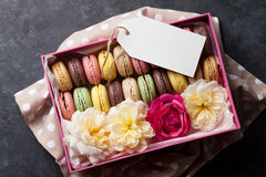Colorful macaroons. Sweet macarons. Colorful macaroons and flowers on stone table. Sweet macarons in gift box. Top view stock photos