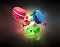 Colorful macaroons are torn to pieces in the air in the dark stock illustration