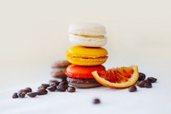Colorful macaroons tower close-up on black background. Taste of coffee and red orange, grain, fruits Stock Images