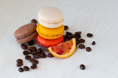 Colorful macaroons tower close-up on black background. Taste of coffee and red orange, grain, fruits Royalty Free Stock Photos