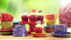 Colorful Mad Hatter style tea party with cupcakes. And rainbow colored polka dot cups and saucers, with bokeh garden background and lens flare, pouring tea Stock Photography