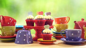 Colorful Mad Hatter style tea party with cupcakes. And rainbow colored polka dot cups and saucers, with bokeh garden background and lens flare, with copy space Stock Image