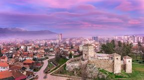 Pink sunset clouds and ancient fortress cityscape royalty free stock photography