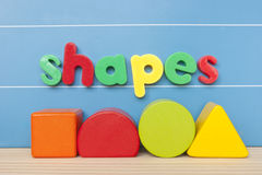 Colorful magnetic letter spelling shapes. Colorful magnetic letters spelling the word shapes on blue board stock photo