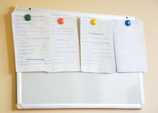 Colorful magnets securing a variety of information. On a bulletin board Royalty Free Stock Images
