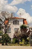 Colorful and majestic old house in Lisbon. Colorful and majestic old house with garden in Lisbon. Old stone facade with big windows in Spring Stock Photo