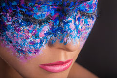 Colorful makeup. Close-up of a young woman with colorful makeup on a black background stock image