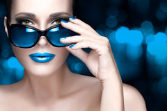 Colorful Makeup. Fashion Model Woman in Black Oversized Sunglasses. Beautiful fashion model girl with Hand on her stylish oversized sunglasses looking at camera stock photos