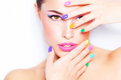 Colorful makeup. Young woman portrait with colorful makeup and nail polish, studio white stock photography