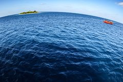 Colorful maldivian dhoni boat floating in wide open ocean with small island in background showing big round world. Colorful maldivian dhoni ferry boat floating Royalty Free Stock Photo