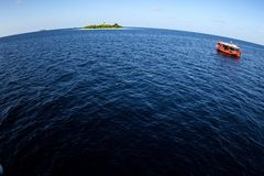 Colorful red  maldivian dhoni ferry  boat floating in wide open ocean with small island in background showing big round world. Colorful maldivian dhoni boat Royalty Free Stock Photography