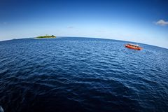 Colorful maldivian dhoni boat sits in open blue waters near a tropical island. Colorful maldivian dhoni ferry boat approaches tropical island in open blue waters Stock Images