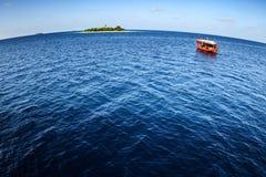 Colorful maldivian dhoni boat in vast blue ocean near a tropical island. Colorful maldivian dhoni ferry boat floats in vast blue ocean near a tropical island Stock Photo