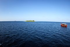 Colorful maldivian dhoni boat sits in open blue waters near a tropical island. Colorful  maldivian dhoni ferry  boat sits in open blue waters near a tropical Royalty Free Stock Images