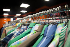 Colorful male shirts in shop. Hangers with colorful male shirts in fashion mall, close up Stock Photo