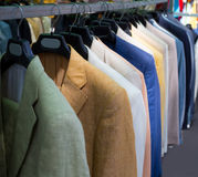 Colorful male suits in row in a hanger Stock Photos