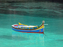Colorful Maltese fisherman's boat. Iuzzu floaring  in crystal clear turquoise water Stock Images