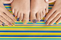 Colorful manicure on short nails and pedicure stock photos