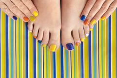 Colorful manicure on short nails and pedicure royalty free stock photography