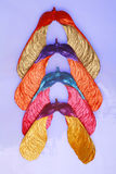 Colorful maple seeds. Vertical display of four maple seeds painted in different colorful vivid shiny colors on bluish tinted tiffany glass background Royalty Free Stock Photos