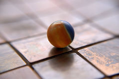 Colorful Marble. Orange and blue marble sitting on copper tiles stock image