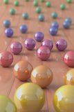 Colorful marble balls on a parquet floor. High quality 3d image of colorful marble balls on a parquet floor Royalty Free Stock Photo