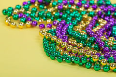 Colorful Mardi Gras beads. On yellow background with copy space royalty free stock photography