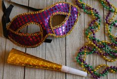 Colorful Mardi Gras mask with beads on wood background. Mardi Gras accessories and decorations for a Fat Tuesday celebration stock photography