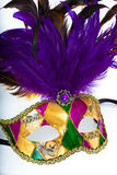 A colorful mardi gras or venetian mask on a white background. A purple, gold, yellow and purple mardi gras or venetian mask on a white background stock photos