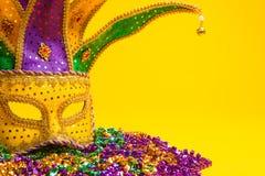 Colorful Mardi Gras or venetian mask on yellow. A festive, colorful mardi gras or carnivale mask on a yellow background. Venetian mask stock photo