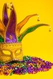 Colorful Mardi Gras or venetian mask on yellow. A festive, colorful mardi gras or carnivale mask on a yellow background. Venetian mask royalty free stock photo