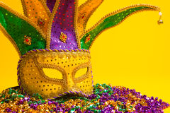 Colorful Mardi Gras or venetian mask on yellow. A festive, colorful mardi gras or carnivale mask on a yellow background. Venetian masks royalty free stock images