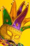 Colorful Mardi Gras or venetian mask on yellow. A festive, colorful mardi gras or carnivale mask on a yellow background. Venetian mask stock photos